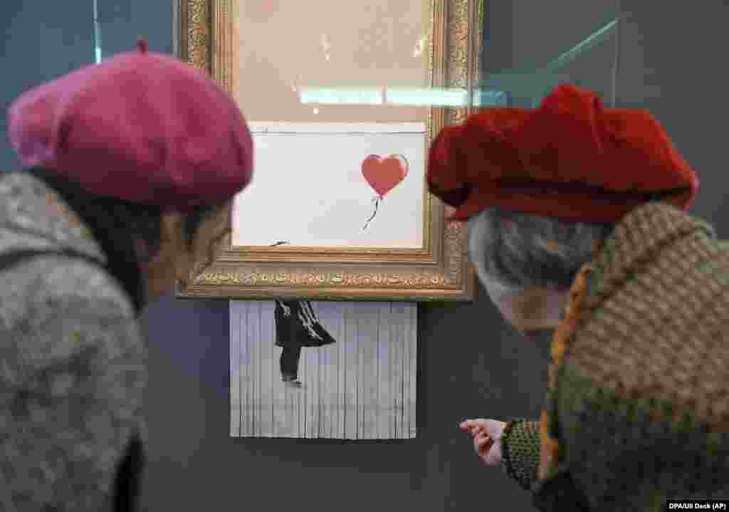 Two women look at the shredded Banksy painting Love Is In The Bin at the Frieder Burda Museum in Baden-Baden, Germany. (dpa/Uli Deck)