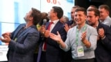 Ukrainian President Volodymyr Zelenskiy (center) applauds with his team as they look at the election results at his party's headquarters in Kyiv on July 21.