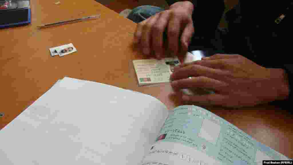 An employee at the registration office fills out information on a new voter card.