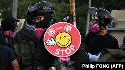 معترض هنگکنگی با سپری که روی آن به چینی و انگلیسی نوشته شده «استاپ» (دست نگه دار) در «چاینیز یونیورسیتی»