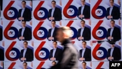 A passerby walks past election posters of the Serbian Progressive Party's (SNS) top candidate for the presidential election, Serbian Prime Minister Aleksandar Vucic, in Belgrade.