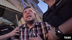 """Полицейские задерживают Василия Дворецкого, одного из активистов группы """"Братья Навального"""". Москва, 13 августа 2013 года."""