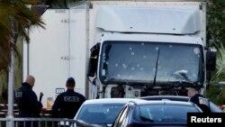 Сотрудники сил безопасности Франции возле грузовика на следующий день после того, как он въехал в толпу, собравшуюся на Английской набережной во французском городе Ницца 14 июля 2016 года.