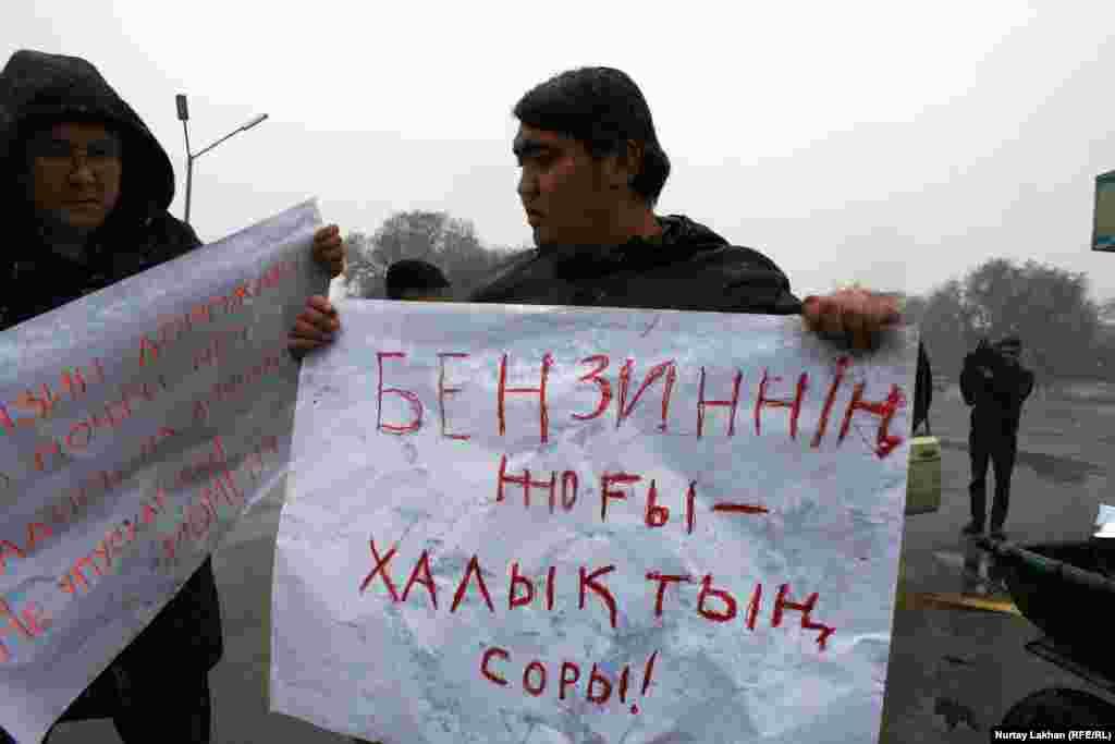Участники акции держали в руках плакаты на казахском и русском языках. На этом плакате на казахском написано: «Бензина нет – это горе народа».