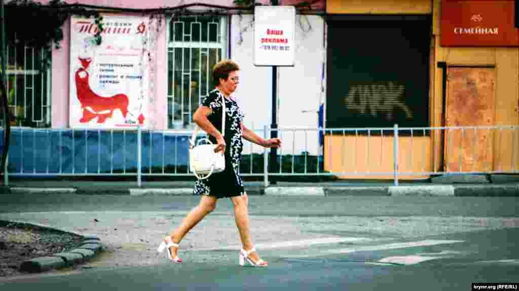 Одинокий пішохід переходить дорогу по вулиці Севастопольській