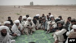 Tribal leaders listen to a U.S. Marine as they gather in the desert for a meeting in Sistani, Helmand Province.