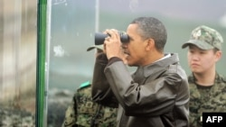 US President Barack Obama looks through binoculars toward North Korea from Observation Post Ouellette during a visit to the Joint Security Area of the Demilitarized Zone (DMZ) near Panmunjom on the border between North and South Korea.