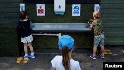 کودکان در حال شستن دستهای خود در مدرسهای در بریتانیا