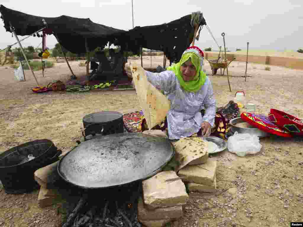 A woman from the Bakhtiari tribe cooks bread in front of the Chogha Zanbil Ziggurat, near Susa, in Iran's Khuzestan Province. (REUTERS/Raheb Homavandi)