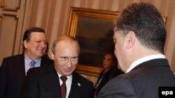 Ресей президенті Владимир Путин (ортада) Украина президенті Петр Порошенкомен амандасып тұр. Милан, 17 қазан 2014 жыл.