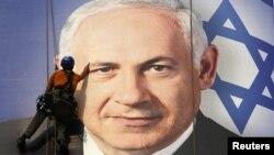 Рабочий приклеивает баннер с изображением премьер-министра Биньямина Нетаньяху, Тель-Авив, 17 января 2013 года.