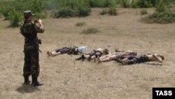 A Russian soldier photographs the bodies of four alleged militants killed in clashes in Daghestan. (file photo)