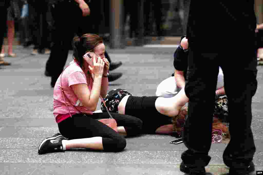 A woman makes a phone call as others attend to an injured person after a car plowed into pedestrians on New York's Times Square on May 18. (AFP/Jewel Samad)