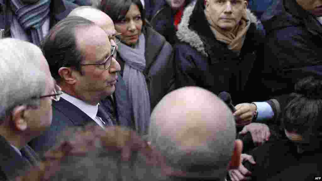 French President Francois Hollande speaks to the press after arriving at the Charlie Hebdo offices.