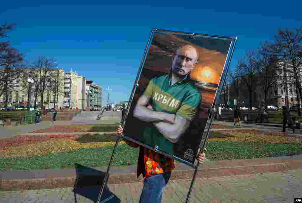 "A man carries a picture depicting Russian President Vladimir Putin in a T-shirt with an inscription reading ""Crimea"" at an open-air political cartoons exhibition in Moscow marking the one-year anniversary of Russia's annexation of the peninsula. The annexation was declared illegal in an overwhelming vote by the UN General Assembly. (AFP/Dmitry Serebryakov)"