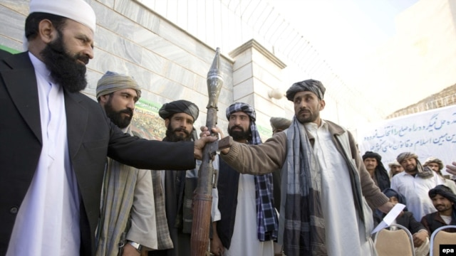 A Taliban militant hands over his weapons in Herat. Can the new incentives persuade more insurgents to lay down their arms?