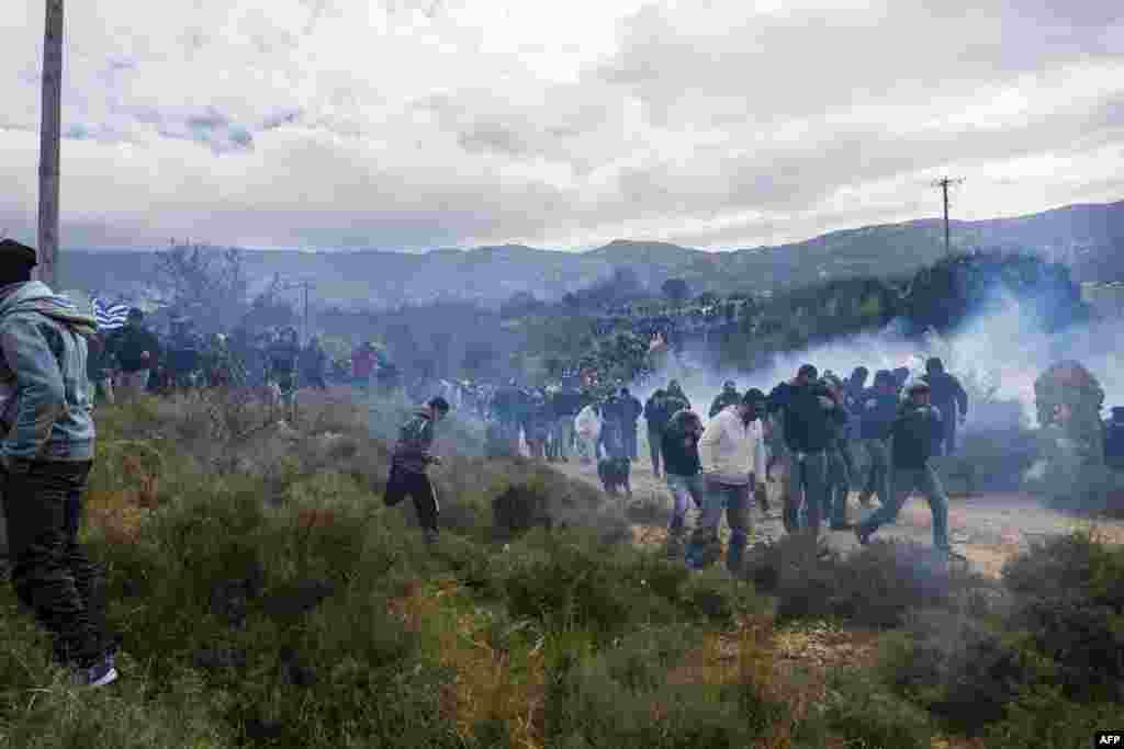 "Tear gas is fired as people protest against the so-called ""hotspot"" being built for refugees and migrants on the Aegean island of Kos. (AFP/Eurokinissi)"