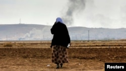 A female Kurdish refugee tries to call relatives who are still trapped in Kobani as thick smoke rises from the Syrian town during heavy fighting between Islamic State militants and Kurdish peshmerga forces on October 27.