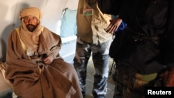 Muammar Qaddafi's son, Saif al-Islam, sits in a plane in Zintan on November 19, after his capture.