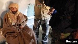 Muammar Qaddafi's son, Saif al-Islam, sits in a plane in Zintan on November 19, after his capture.