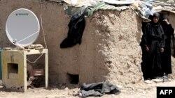 A TV satellite dish sits next next to a makeshift home in Baghdad's Al-Dora slum. (file photo)