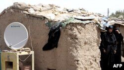 A TV satellite dish sits next next to a makeshift home in Baghdad's al-Dora slum (file photo)