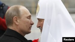 President Vladimir Putin (left) welcomes Patriarch Kirill during a ceremony to mark National Unity Day in Moscow on November 4.