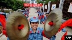 Люди, одетые в красноармейскую форму, выступают в честь открытия съезда КПК в Йияне в центральной провинции Китая Цзянси