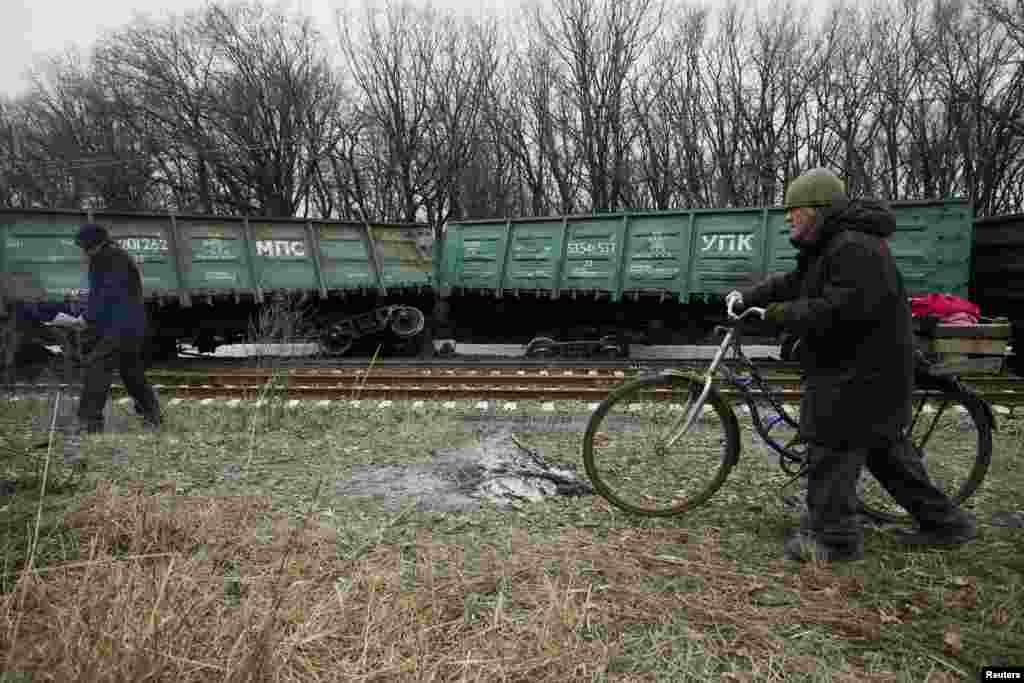People walk past a train that was derailed after a blast on a rail track in the rebel-controlled town of Yasynuvata, near Donetsk, in Ukraine. (Reuters/Alexander Ermochenko)