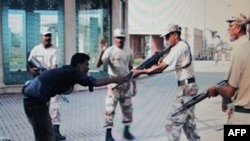 The Awaz News TV channel image from June 10, 2011, shows paramilitary soldiers shooting unarmed Pakistani youth Sarfaraz Shah (left) in Karachi on June 8.