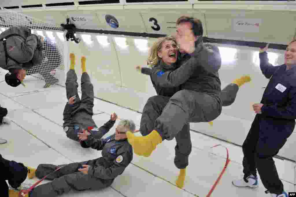 Civilian passengers of France's Airbus A330 Zero-G, who are not astronauts or scientists, enjoy weightlessness during the first zero-gravity flight for paying passengers in Europe. All boarding cards, costing 6,000 euros, were sold for the years 2013 and 2014. Zero gravity is simulated by flying a series of parabolic flight maneuvers. (AFP/Mehdi Fedouach)