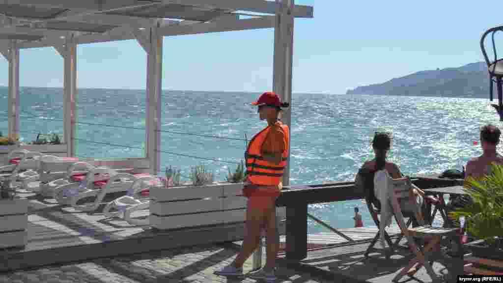 Er solâriy yanında qurtarıcılar nevbetçilik yapa, olarnıñ işi - turistler iskelede deñizge sıçramasın, dep közetmek