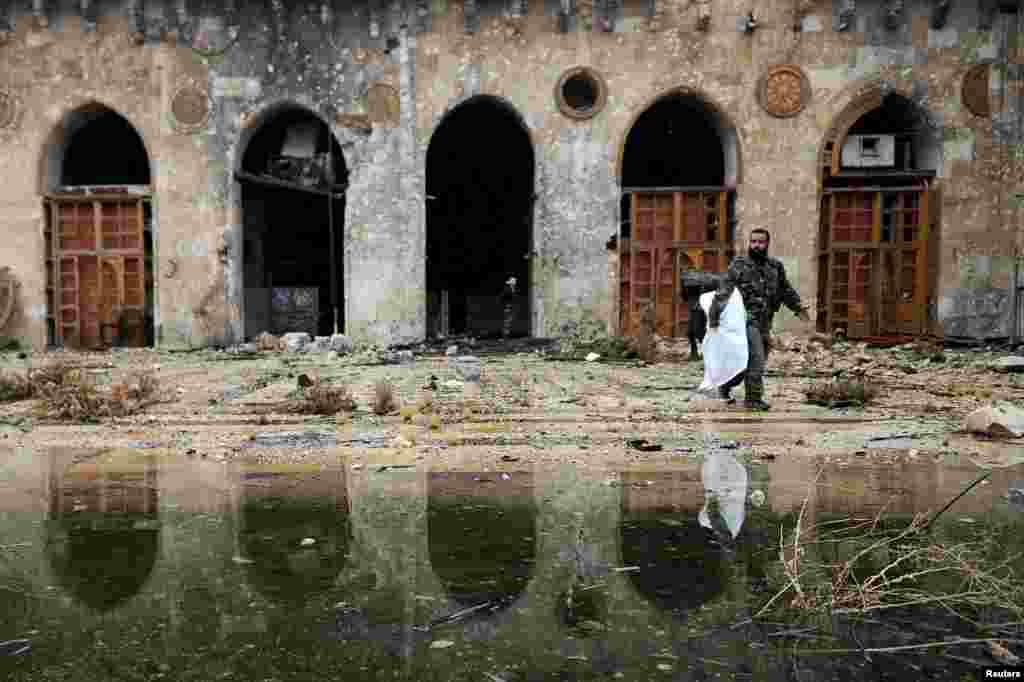 سرباز سوری در کنار آنچه از مسجد اموی (مسجد جامع) در حلب مانده؛ مناره این مسجد هزار سال پیش ساخته شده بود.