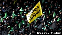 "Female regime supporters are seen at Azadi stadium during the speech of the Iranian Supreme Leader Ayatollah Ali Khamenei in Tehran. The yellow banner says ""Death to Israel"". October 4, 2018."