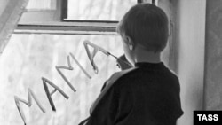 "A boy in a Russian orphanage writes the word ""mother"" on a window pane."