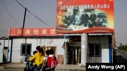 Қытай президенті Си Цзиньпин пен ұйғыр ұлтының өкілдері бейнеленген көшедегі баннердің қасынан өтіп бара жатқан мотоцикль мінген ұйғыр әйелі мен балалар. Шыңжаң, Қытай, 20 қыркүйек 2020 жыл.