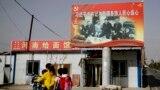 На этой фотографии, сделанной 20 сентября 2018 года, уйгурка везет детей мимо фотографии, на которой президент Китая Си Цзиньпин держится за руки с уйгурскими старейшинами в Новой деревне Единства в Хотане.