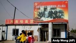 На этой фотографии, сделанной 20 сентября 2018 года, уйгурка везет детей мимо фотографии, на которой председатель Китая Си Цзиньпин держится за руки с уйгурскими старейшинами в Новой деревне Единства в Хотане