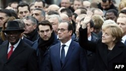 German Chancellor Angela Merkel (right) waves while taking part with French President Francois Hollande (center) in a rally in Paris on January 11.