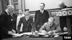 Міністр закордонних справ СРСР В'ячеслав Молотов (праворуч, сидить) підписує пакт Молотова-Ріббентропа. Третій ліворуч – генеральний секретар ЦК ВКП(б) Йосип Сталін. Москва, 23 серпня 1939 року