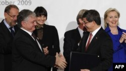 Switzerland -- Turkish Foreign Minister Ahmet Davutoglu (2ndR) and his Armenian counterpart Eduard Nalbandian shake hands as they hold signed Turkish-Armenian protocols, Zurich, 10Oct2009.