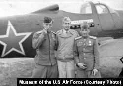 """Американские и советские летчики на фоне американского исстребителя """"Белл P-39 Аэрокобра"""""""