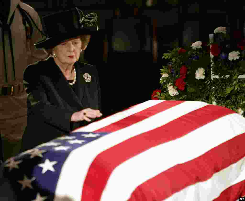 Margaret Thatcher reaches out to touch the flag-draped coffin of former U.S. President Ronald Reagan as he lies in state at the U.S. Capitol in June 2004.