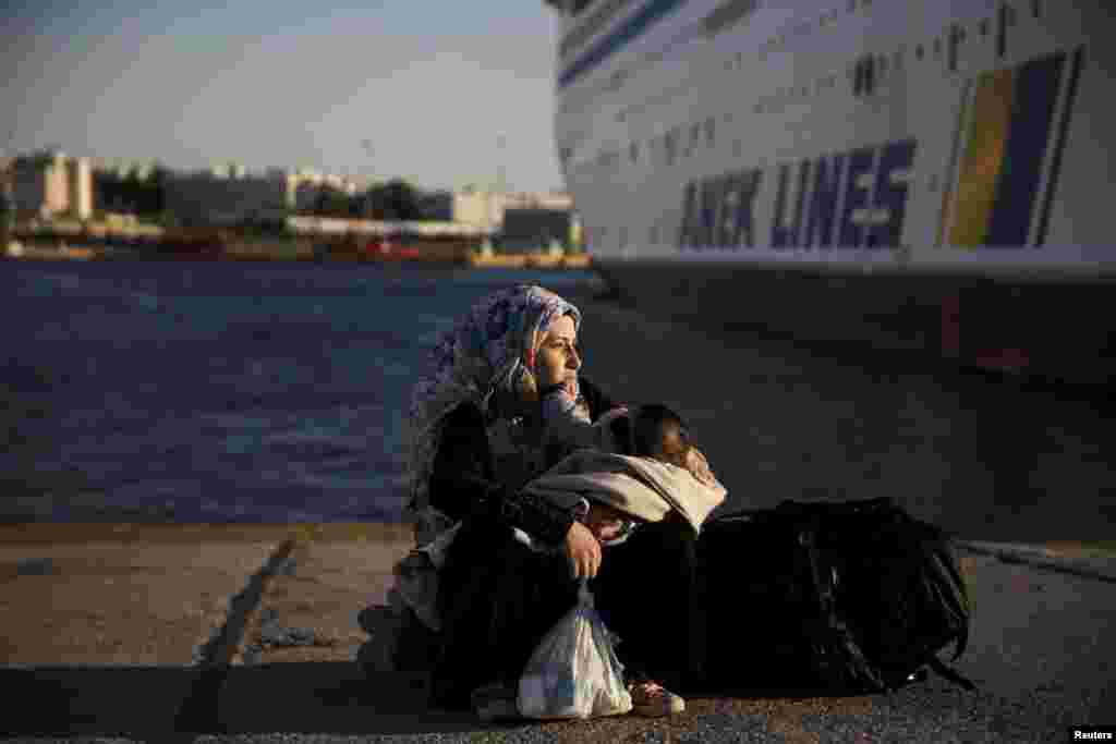 A Syrian refugee holds her baby after arriving aboard the passenger ferry Eleftherios Venizelos from the island of Lesbos at the port of Piraeus, near Athens. (Reuters/Alkis Konstantinidis)