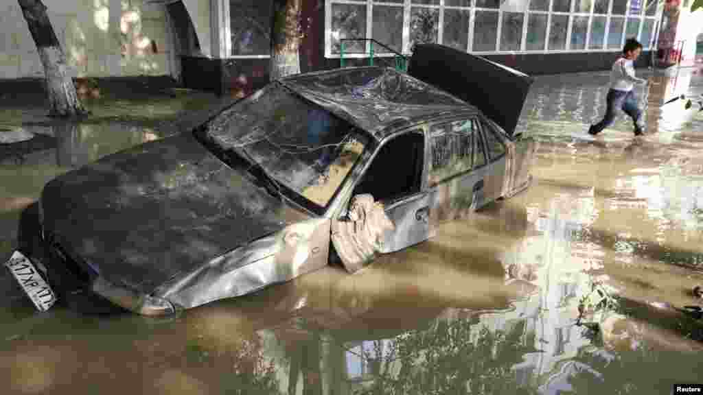 A local resident passes by a damaged car stuck in a flooded street in Krymsk.