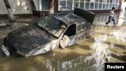 A local resident passes by a damaged car stuck in a flooded street in the town of Krymsk in Russia's Krasnodar region.