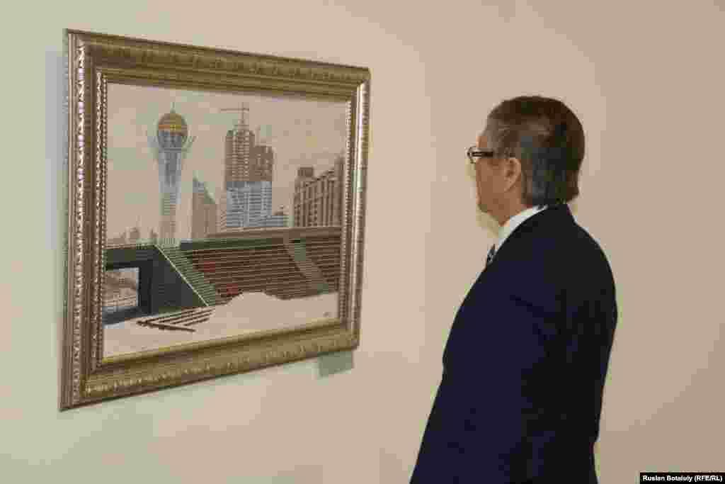 Посетитель смотрит на картину Калиоллы Ахметжана «Арайлы Астана» («Озаренная Астана»).