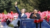 NOTRH KOREA - North Korean leader Kim Jong Un (right) and South Korean President Moon Jae-in (left) wave to Pyongyang citizens from an open-topped as they drive through Pyongyang on September 18, 2018