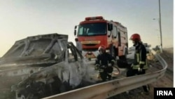 Emergency workers remove a car which exploded into flames after Iranian police reportedly opened fire on it. Three Afghan migrants died in the incident.