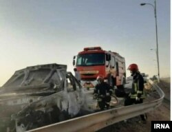 Emergency workers remove a car which exploded into flames after Iranian police reportedly opened fire on it in early June. Akram was traveling in the car (file photo).